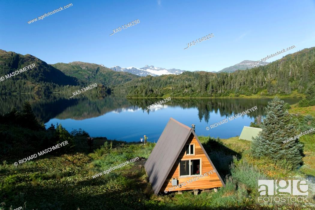 Stock Photo: US Forest Service cabin, mother and daughter enjoying the view, Shrode Lake, Prince William Sound, Alaska, USA.