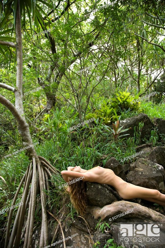 Stock Photo: Nude Caucasian young adult woman in lush forest stretched out over rock.
