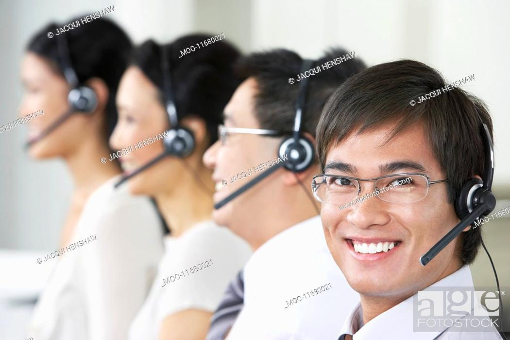 Stock Photo: Row of customer service representatives wearing telephone headsets in office head and shoulders.