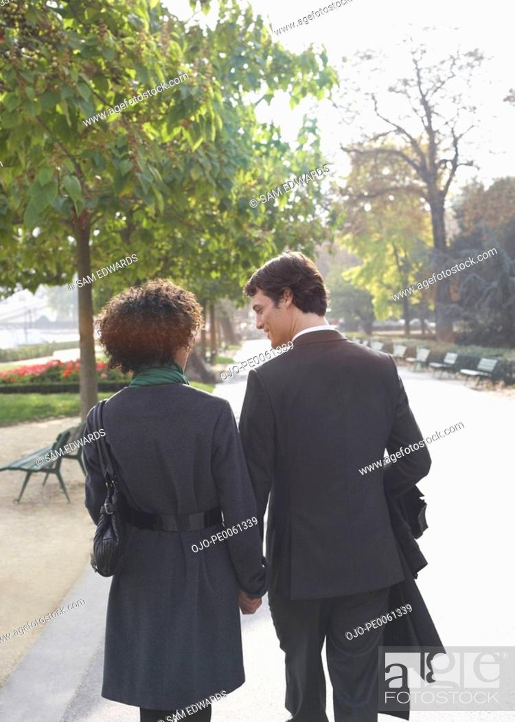 Stock Photo: Couple walking outdoors holding hands.