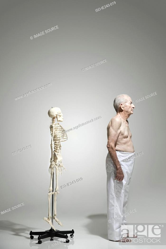 Stock Photo: Elderly man standing near a skeleton.