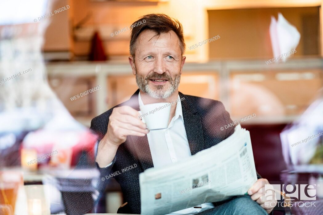 Stock Photo: Portrait of smiling mature businessman with newspaper sitting in a coffee shop drinking coffee.
