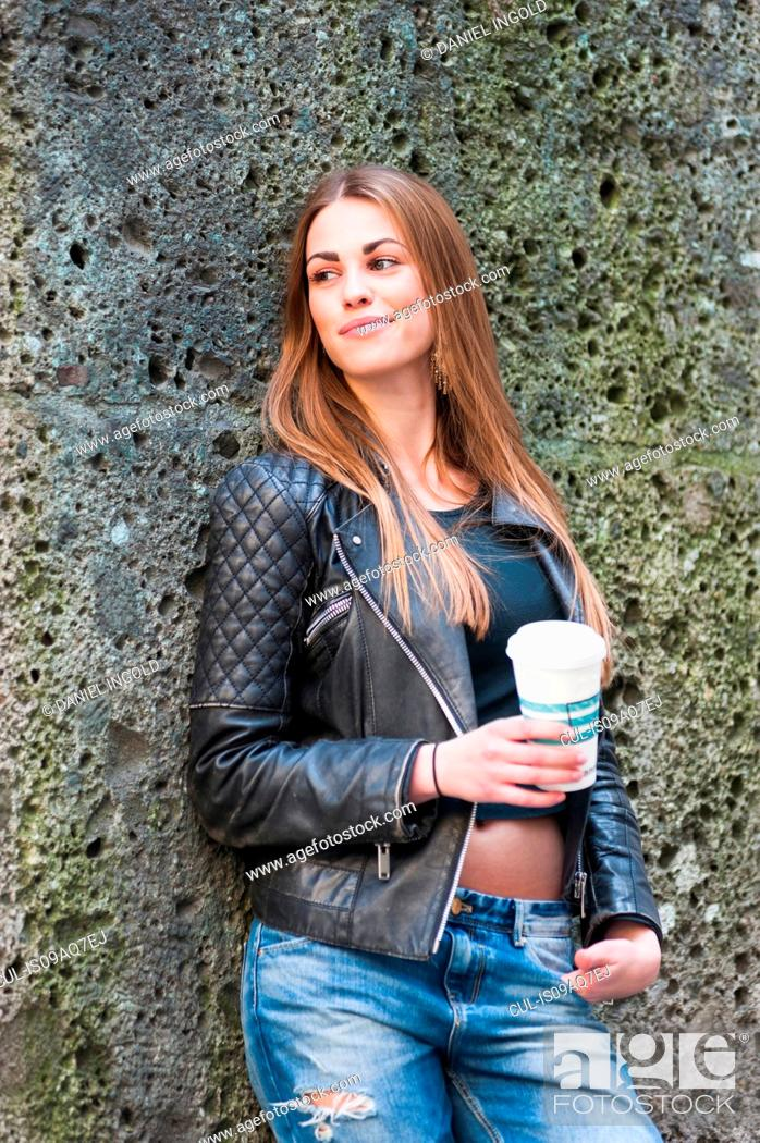 Young Stylish Woman Leaning Against Old Wall Drinking Coffee
