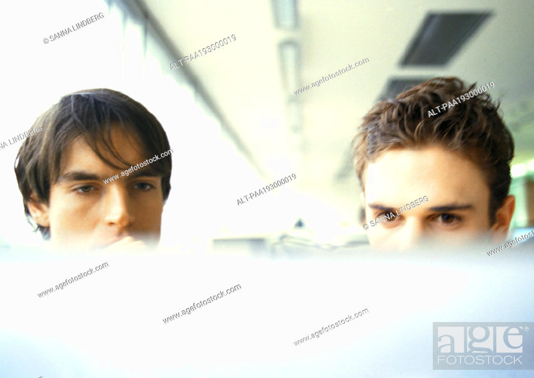 Stock Photo: Computer screen, rear view, blurred in foreground, businessmen's heads, upper section in background.