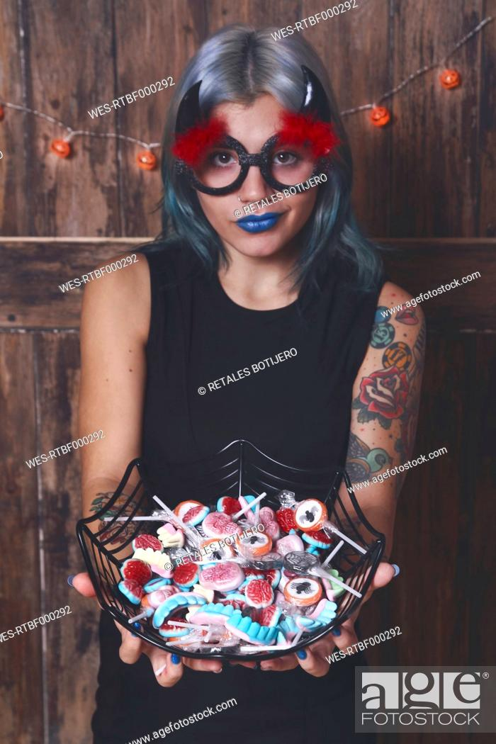 Stock Photo: Masqueraded young woman offering Halloween candies.
