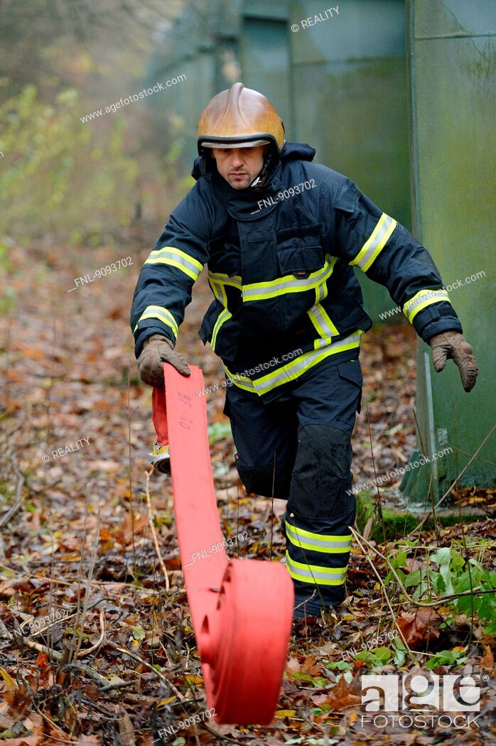 Stock Photo: A fireman is rolling out a tube.
