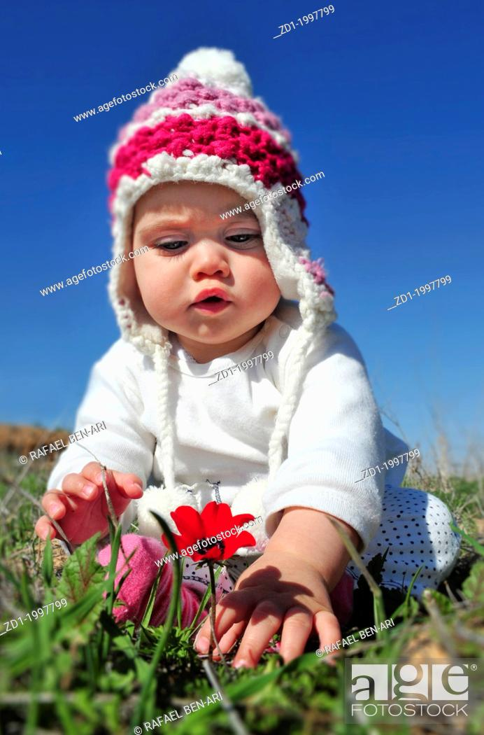 Stock Photo: A toddler sits in a green field and play with flowers.