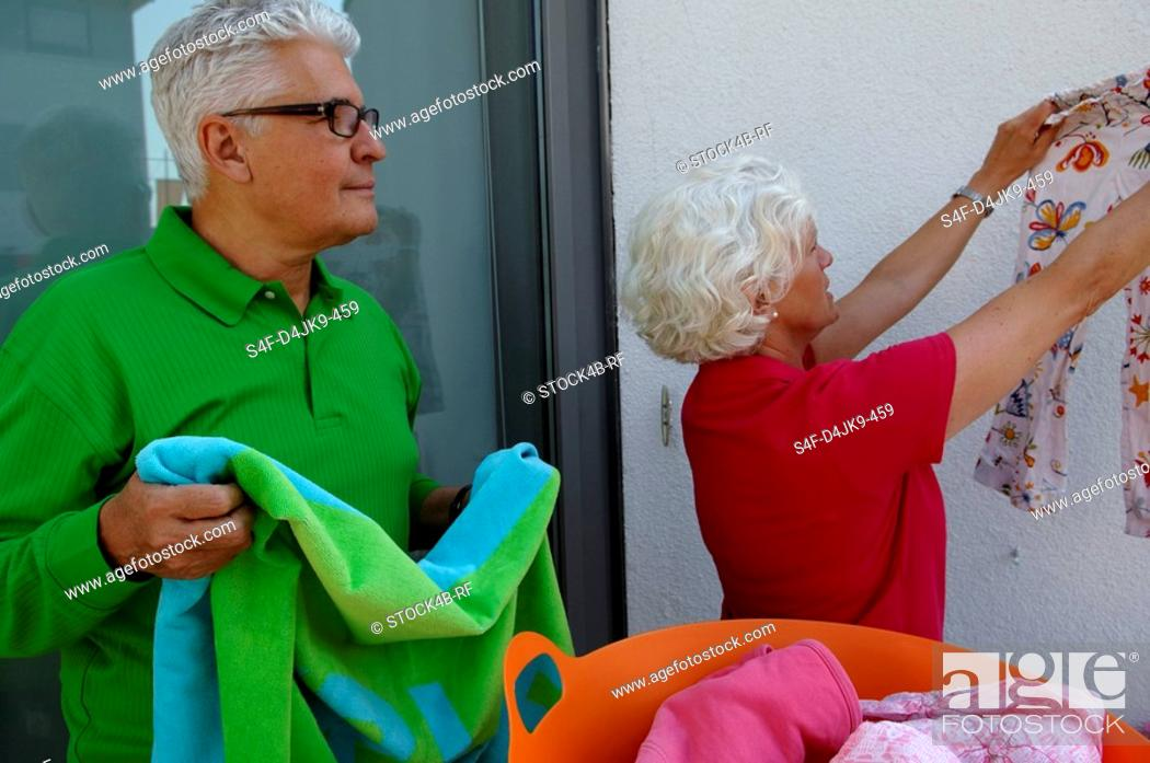 Stock Photo: Senior couple hanging out the laundry.