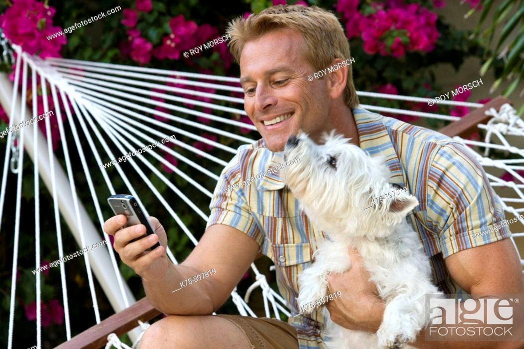 Stock Photo: Happy man in hammock with his pet dog.
