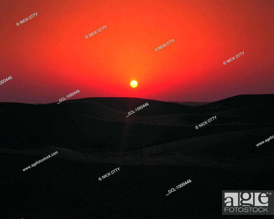 Stock Photo: Red sky at sunset over the desert.