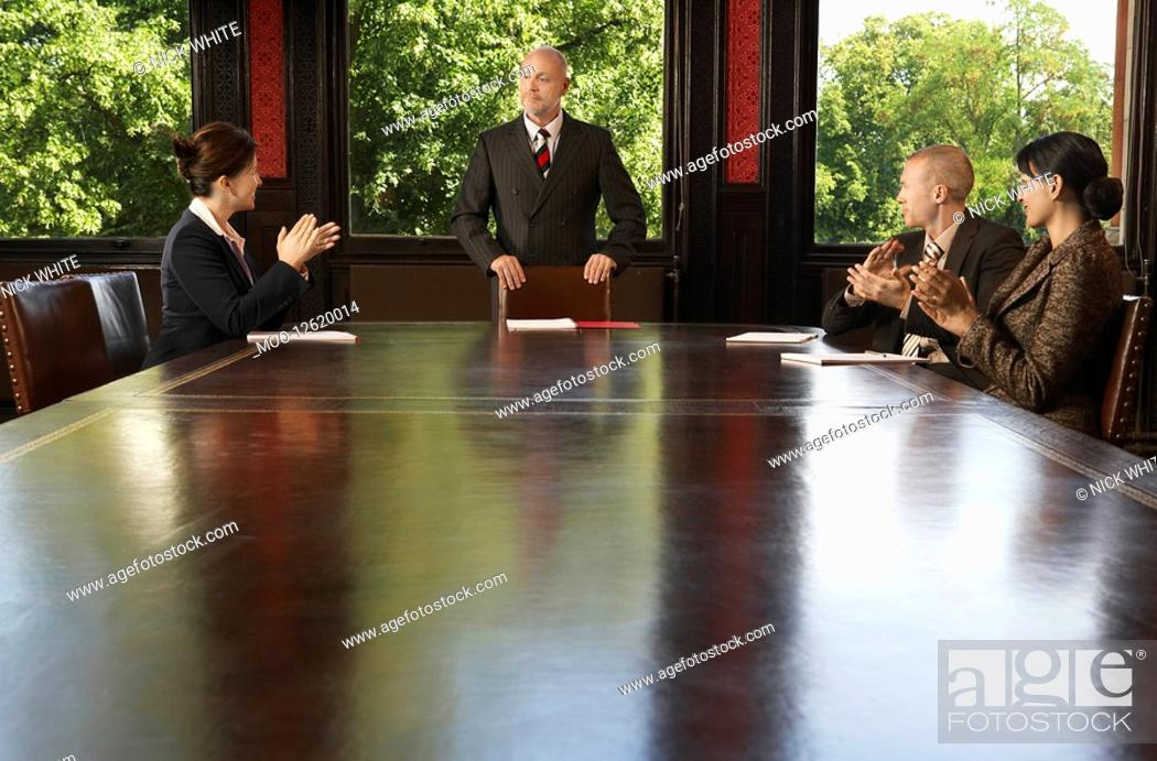 Stock Photo: Businesspeople around boardroom table applauding man.