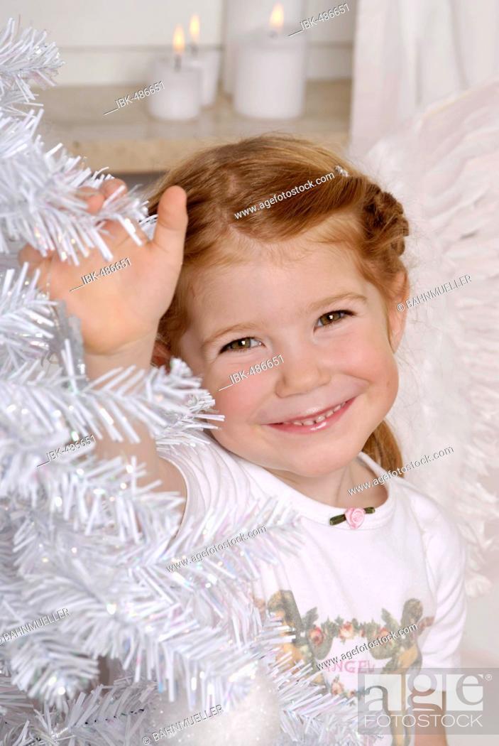 Stock Photo: Child decorates a white christmas tree.