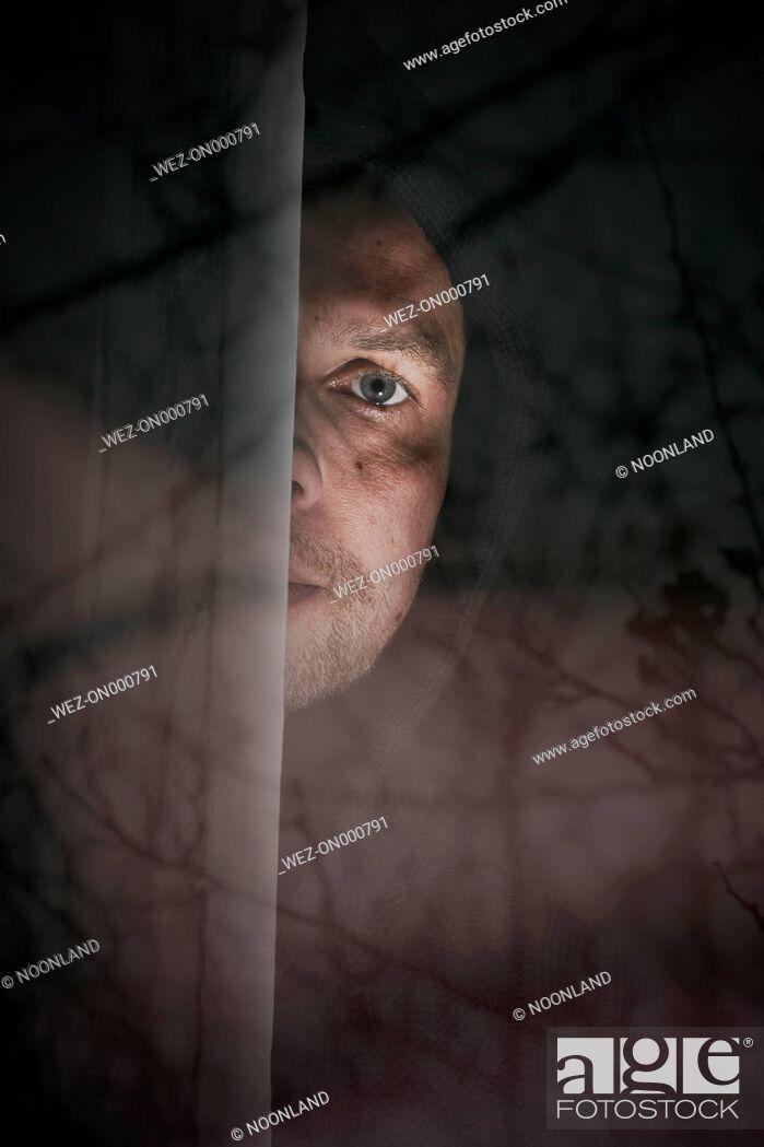 Stock Photo: Man peeking from behind windowpane.