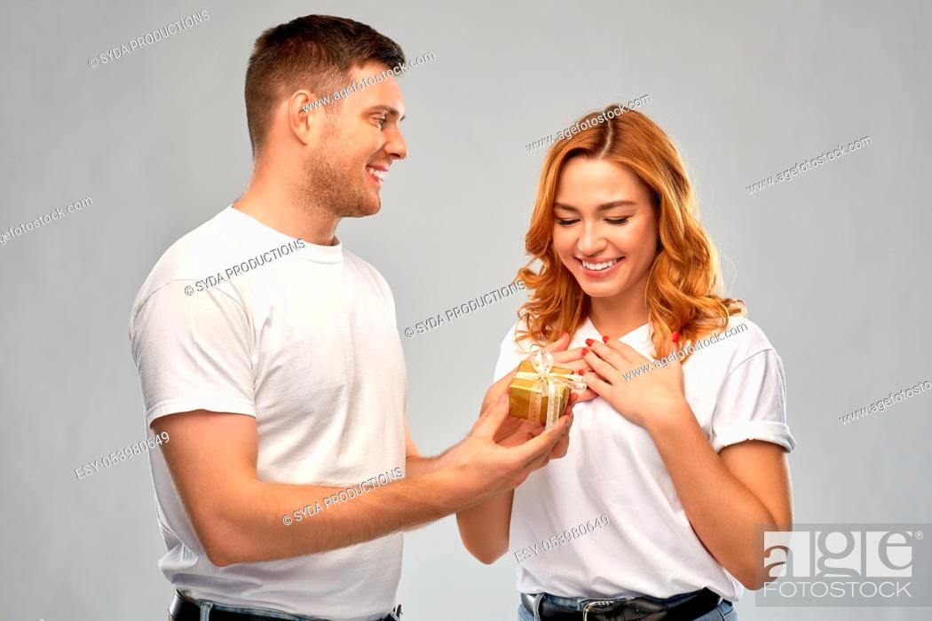 Stock Photo: happy couple in white t-shirts with christmas gift.
