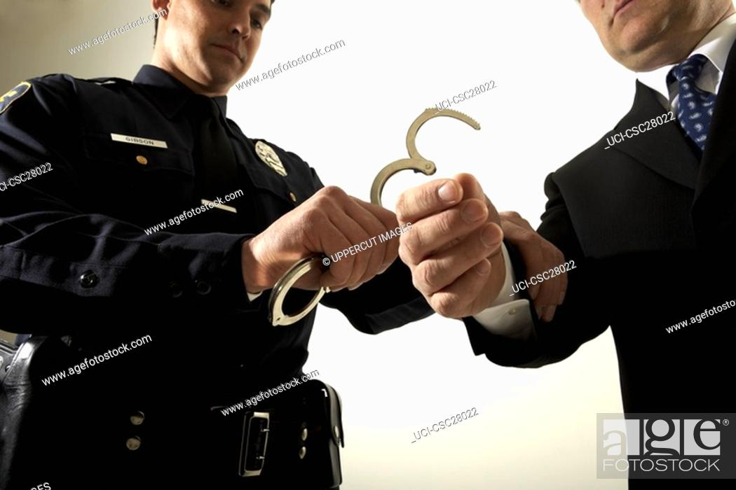 Stock Photo: Male police officer handcuffing businessman.