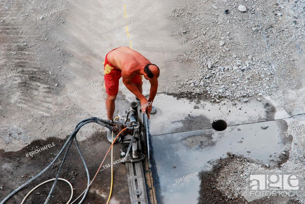 Stock Photo: A worker uses disassemble a concrete saw when a highway bridge.