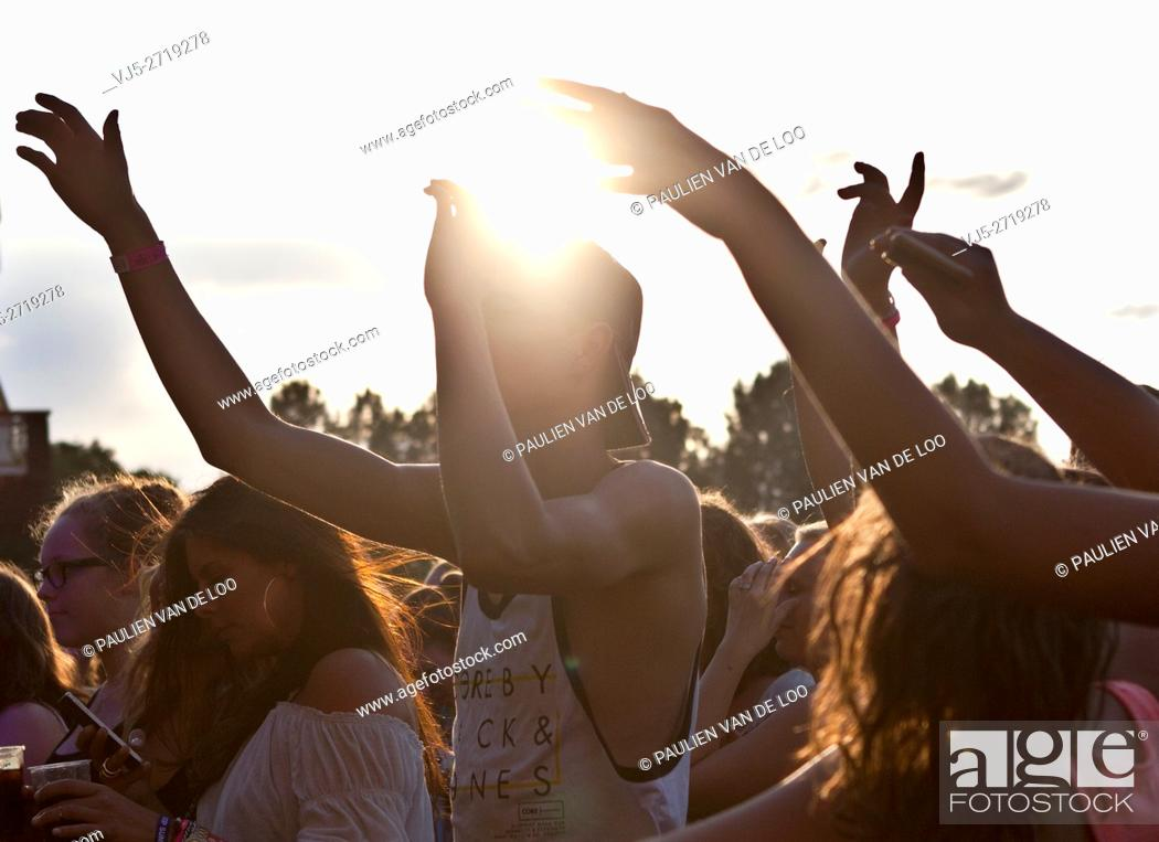 Stock Photo: Beek en Donk, Netherlands, crowd is dancing and cheering during the sunset.