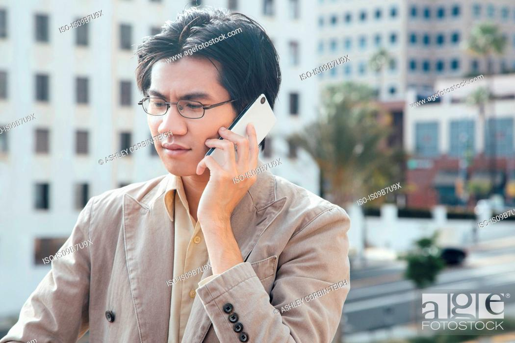 Stock Photo: Young man outdoors, using smartphone.