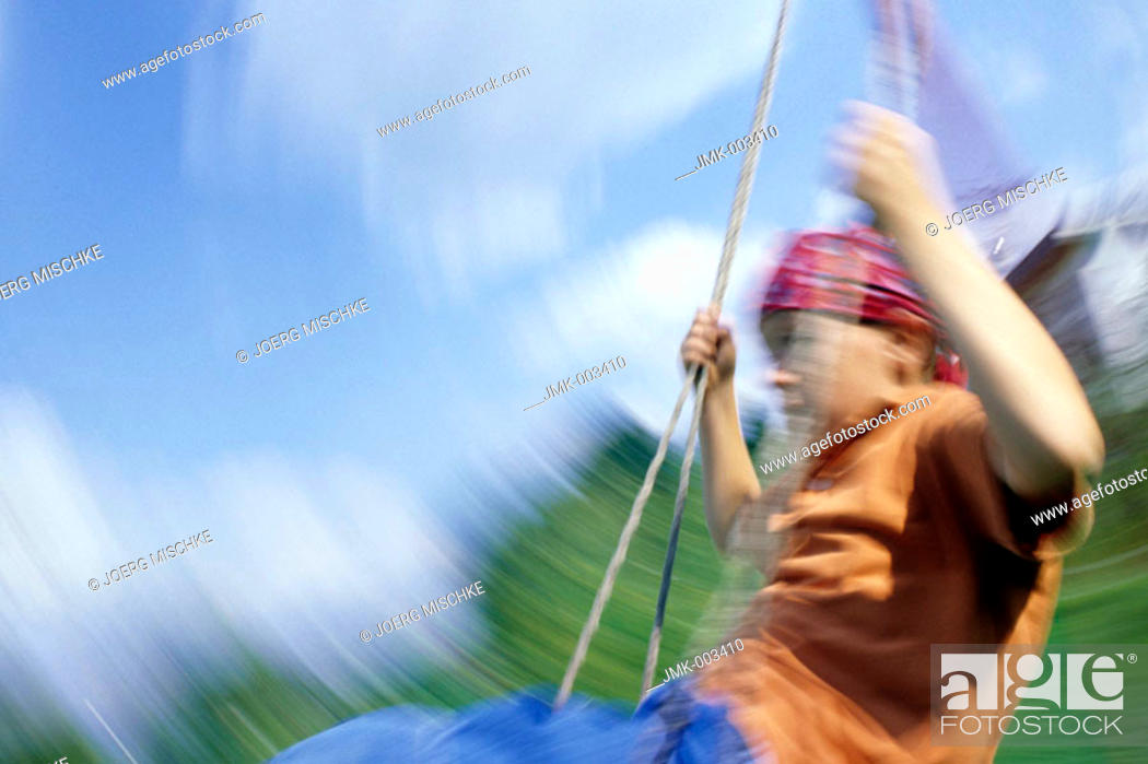 Stock Photo: A boy, 5-10 years old, swinging outside in the garden in summer, blurred.
