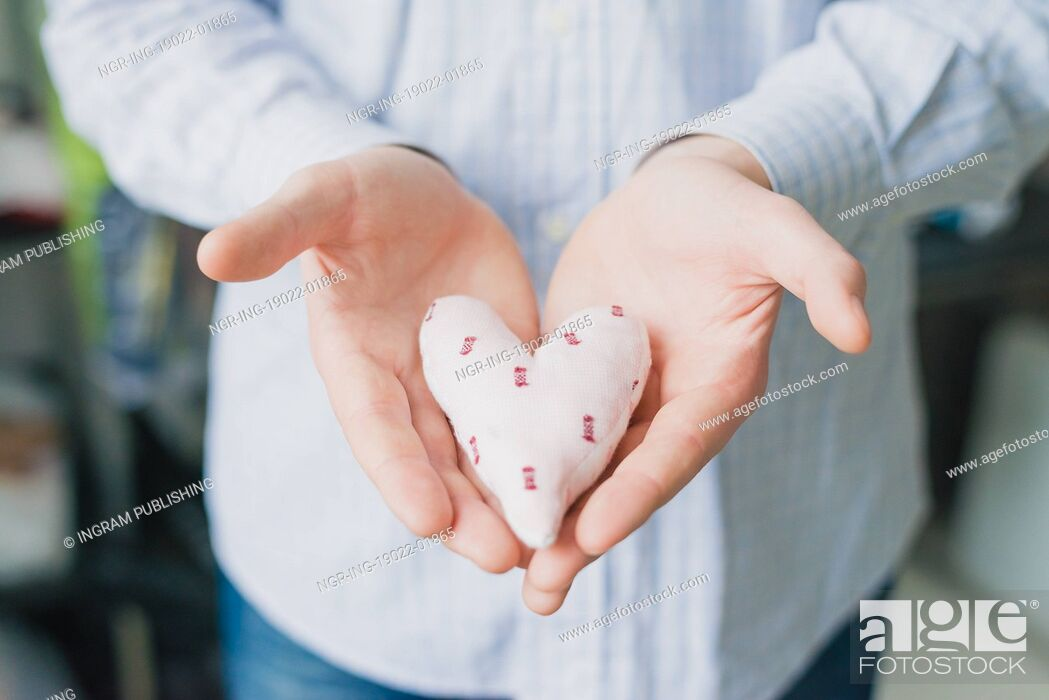 Stock Photo: A man holds a heart in his hand.