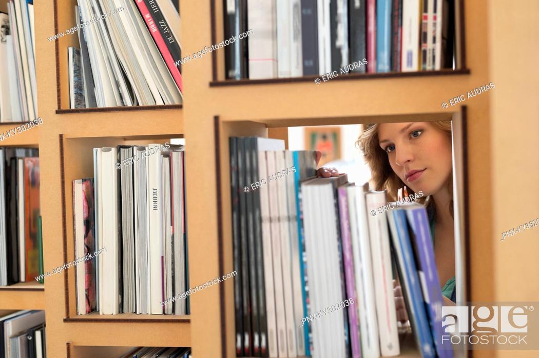 Stock Photo: Woman choosing books from a bookshelf.