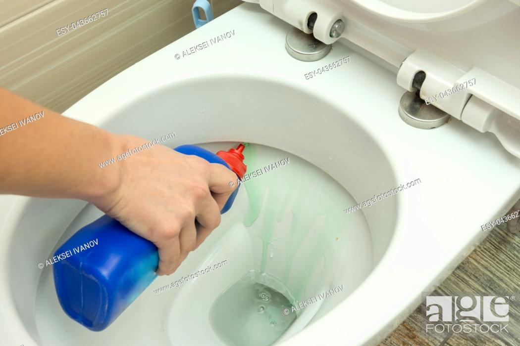 Stock Photo: The hand puts a liquid detergent under the rim of the toilet bowl.