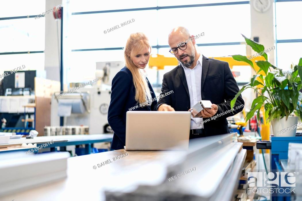 Stock Photo: Businessman and businesswoman with laptop and workpiece talking in factory.