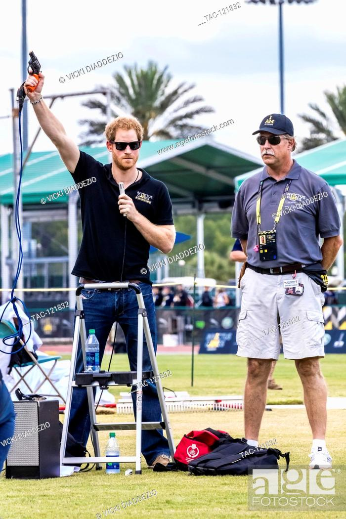 Prince Harry fires the starter pistol to begin a track and field