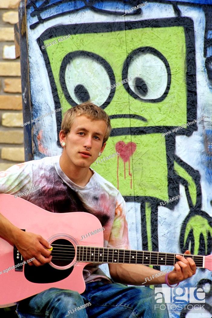 Imagen: Teenager Playing Pink Guitar next to Graffiti, Winnipeg, Manitoba.