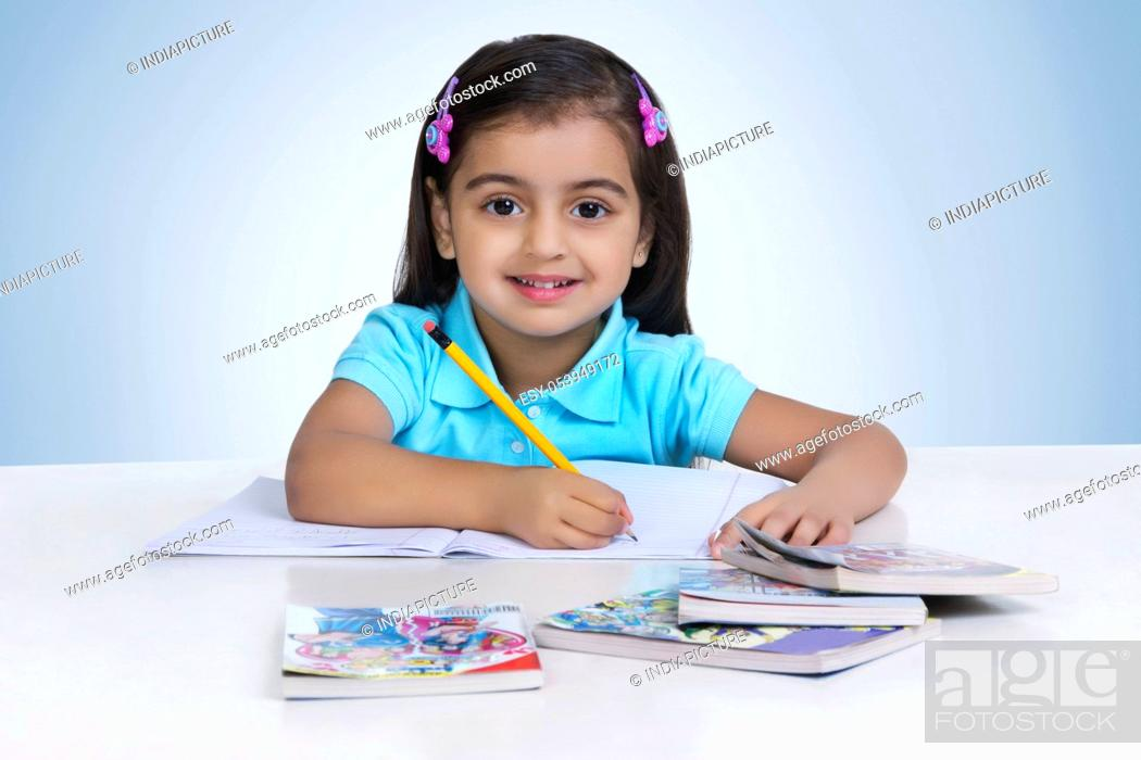 Stock Photo: Portrait of cute girl studying against blue background.