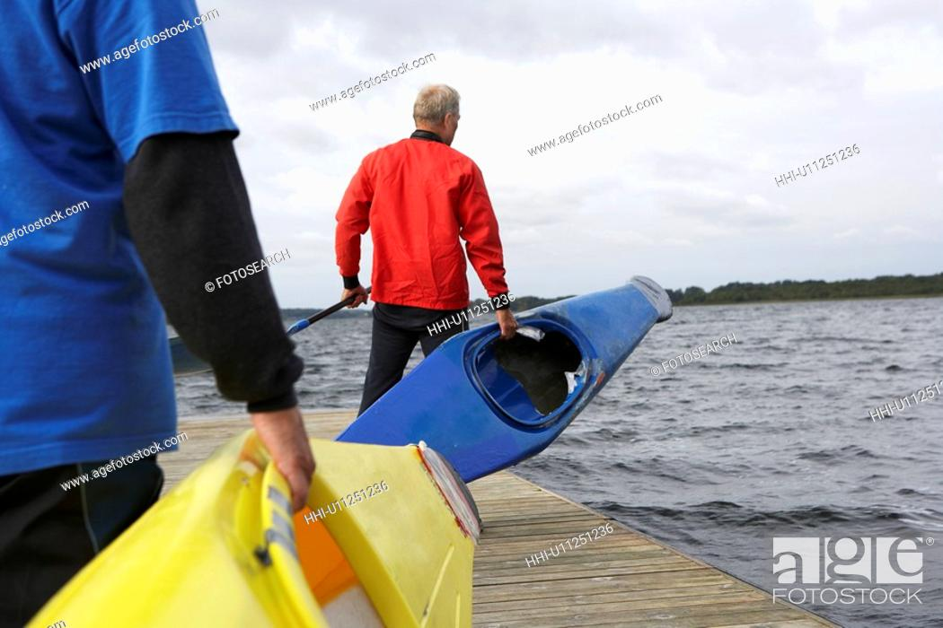 Stock Photo: Two senior men carrying kayaks.