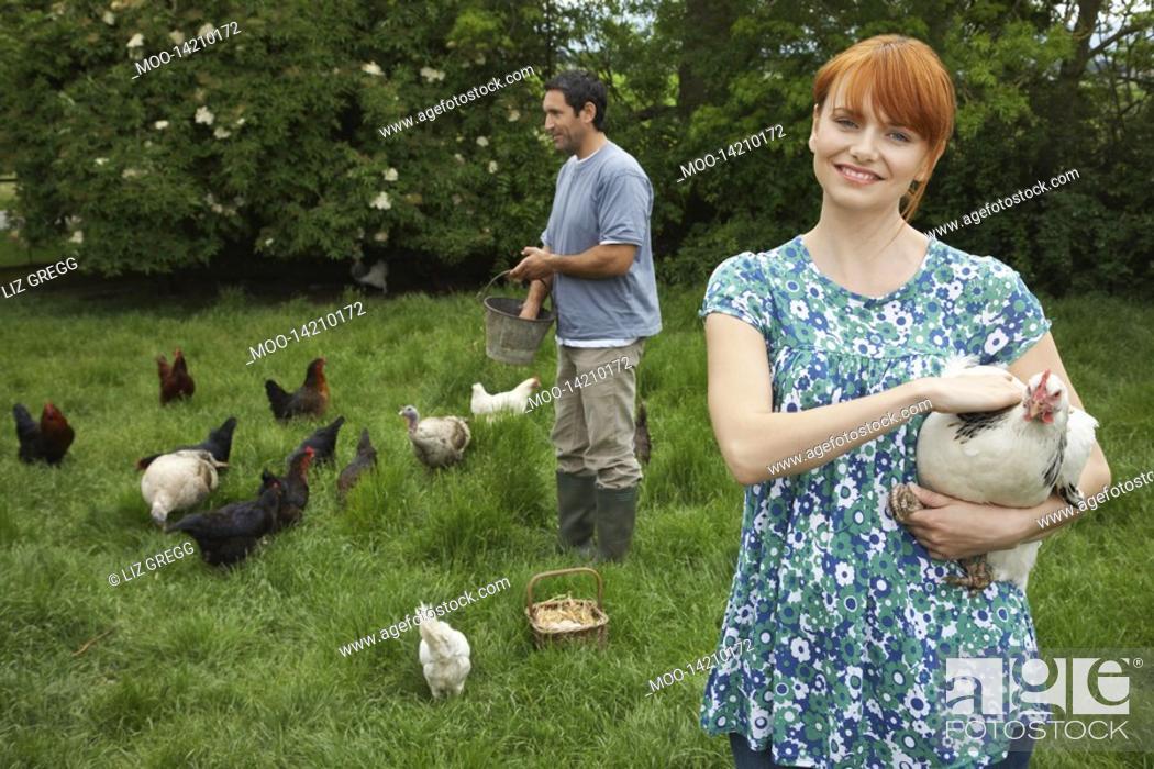 Stock Photo: Couple feeding hens in garden portrait.