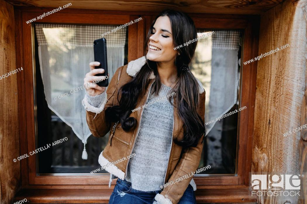 Stock Photo: Happy young woman at the window of a wooden house taking a selfie.