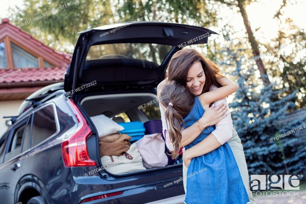 Stock Photo: Mother and daughter embracing in front of their car.