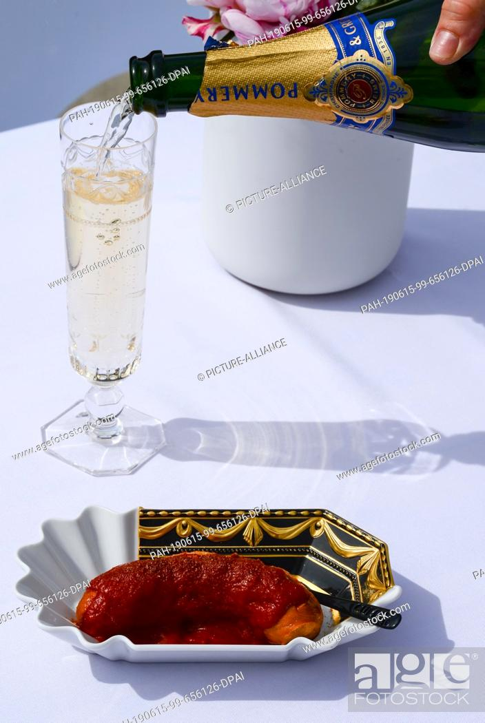 Stock Photo: 14 June 2019, Berlin: A Currywurst is served on a KPM Currywurst bowl with Kurland relief and champagne at the Court Festival of the Royal Porcelain Manufactory.