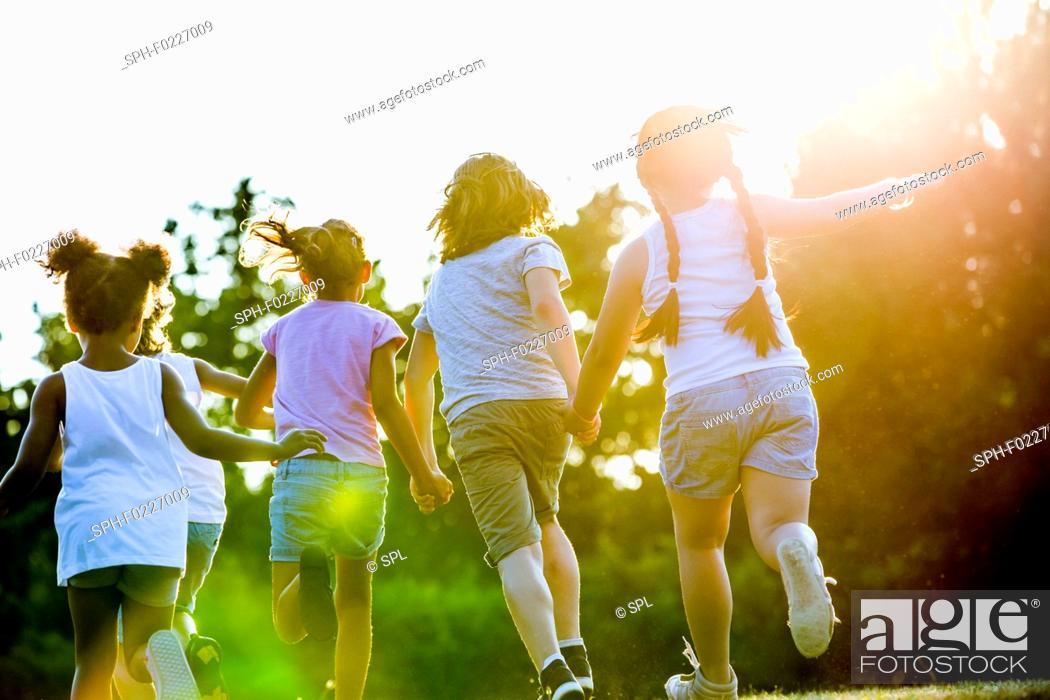 Stock Photo: Children holding hands and running.