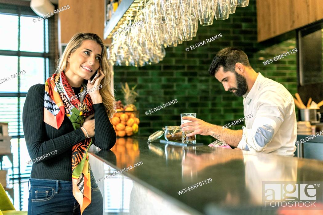 Stock Photo: Smiling woman on cell phone at the counter of a bar with barkeeper preparing a cocktail.