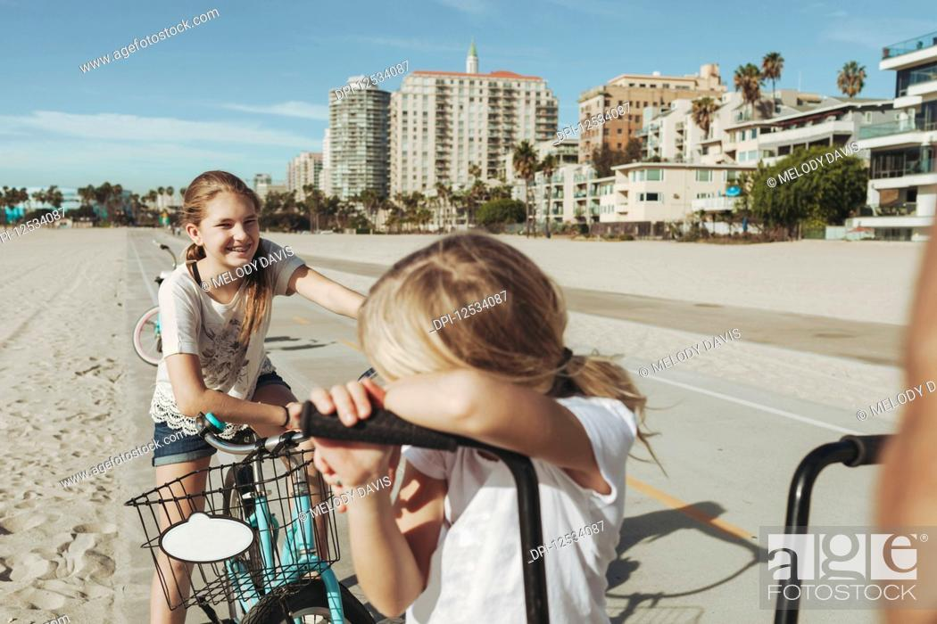 Imagen: Sisters ride bikes along the beach in Long Beach; Los Angeles, California, United States of America.