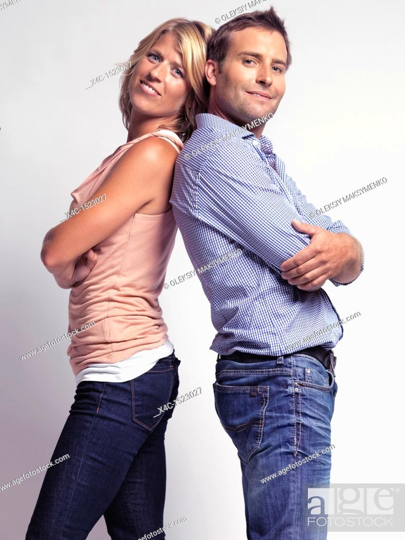 Stock Photo: Smiling casually but with style dressed young man and a woman standing back to back, wearing jeans isolated on gray background.