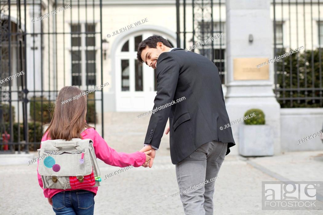 Stock Photo: Girl walking towards school with her father.