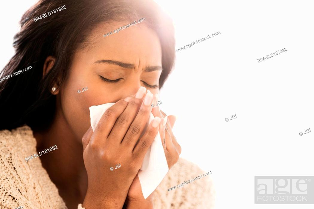Stock Photo: Mixed race woman blowing her nose.