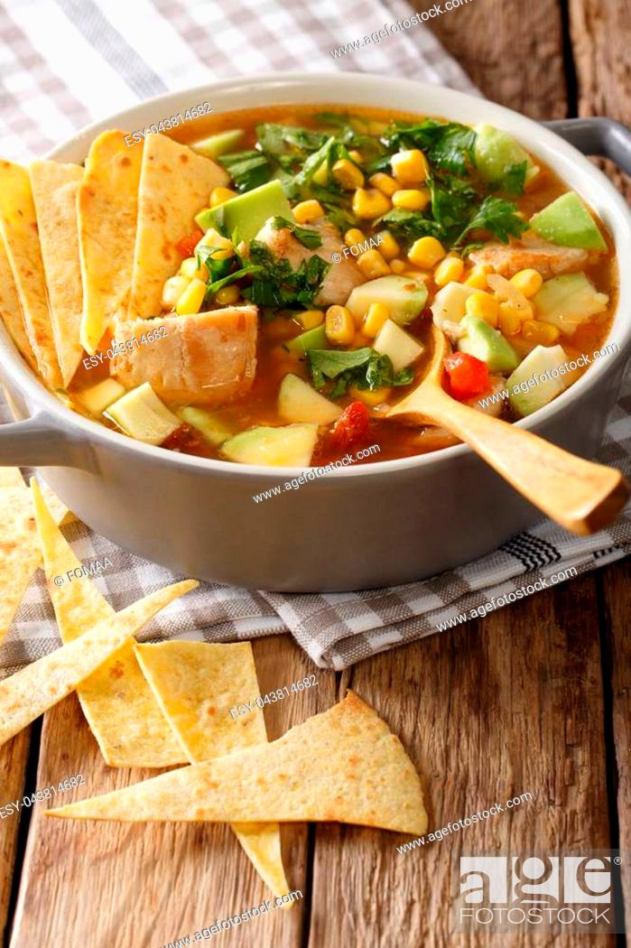 Stock Photo: Mexican food: tortilla soup with chicken, tomatoes, avocado and corn close-up in a saucepan on a table. vertical.