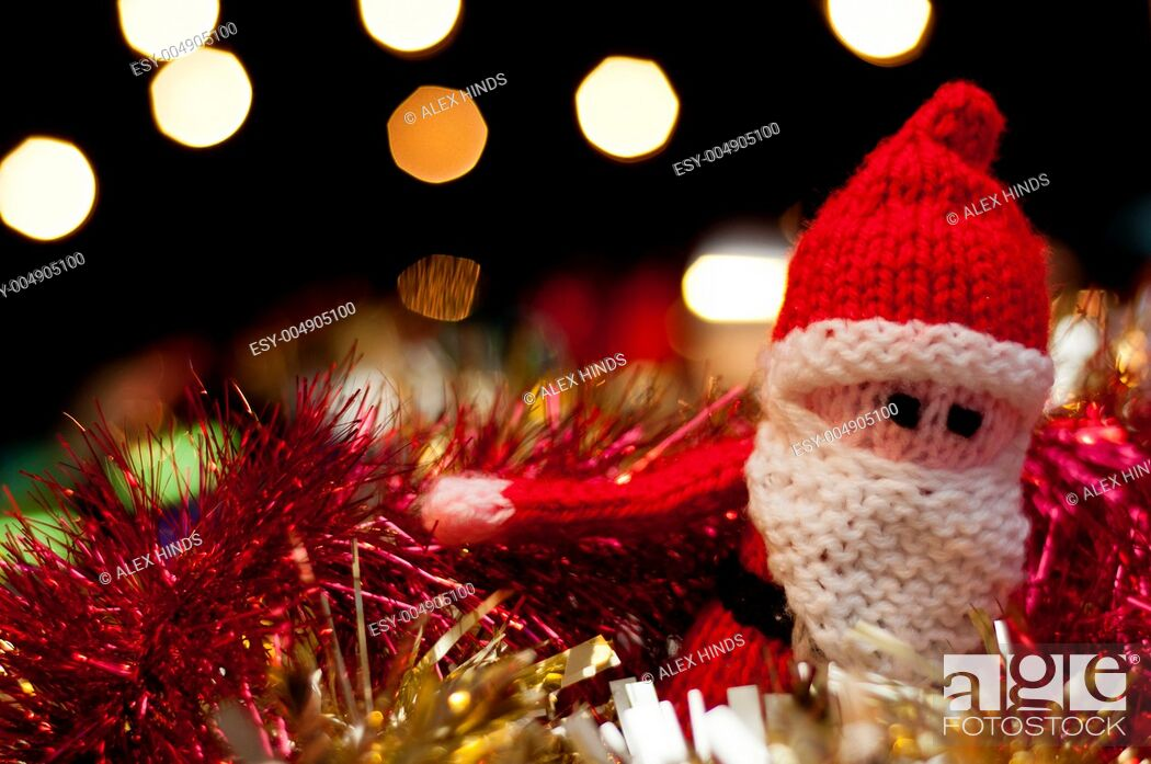 Stock Photo: Father Christmas Santa Claus toy amidst tinsel and baubles.