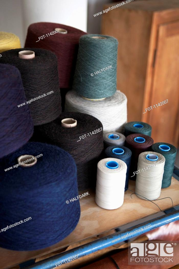 Stock Photo: Spools of cotton on a workbench.