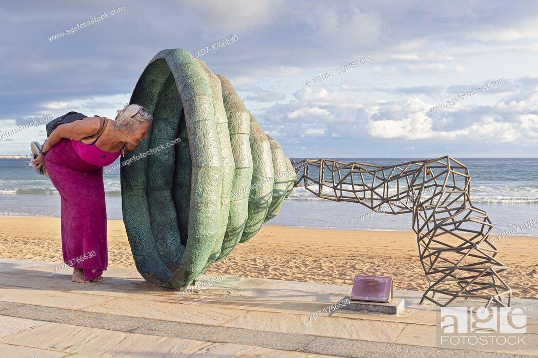 Imagen: Europe, Spain, Gipuzkoa, Zarautz Beach with Sculpture shaped like a horn being investigated by a woman tourist.