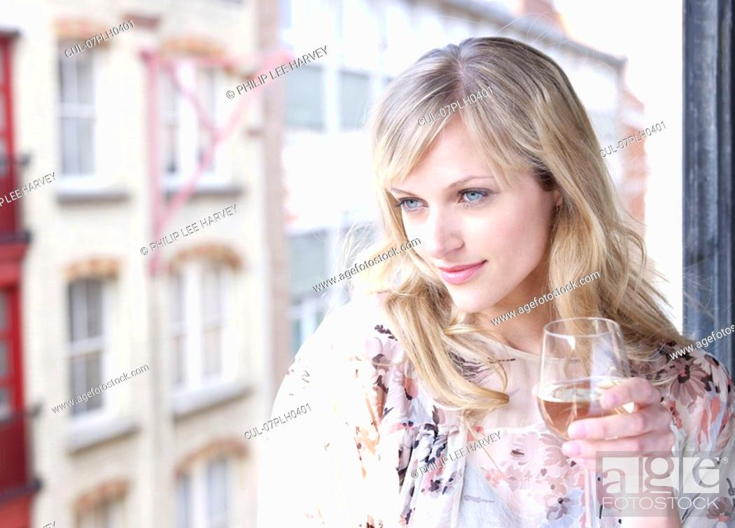 Stock Photo: Woman against window with wine glass.