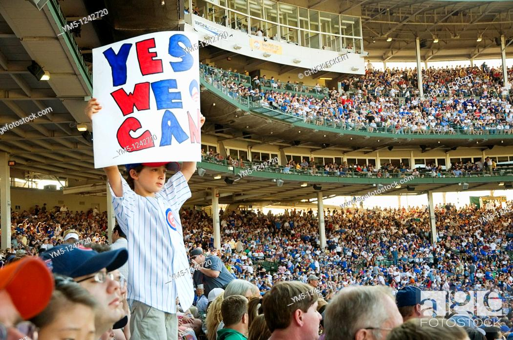 Stock Photo: Young Chicago Cubs fan holding up positive message sign saying 'Yes We Can ' at Wrigley Field.