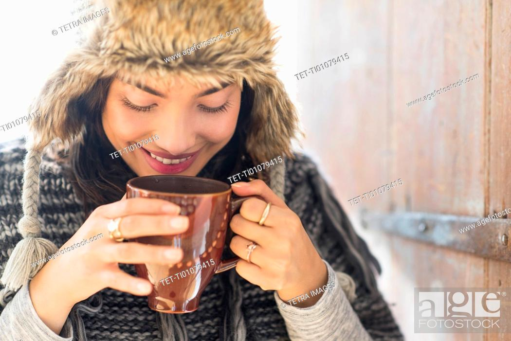 Stock Photo: Portrait of smiling young woman drinking from mug.
