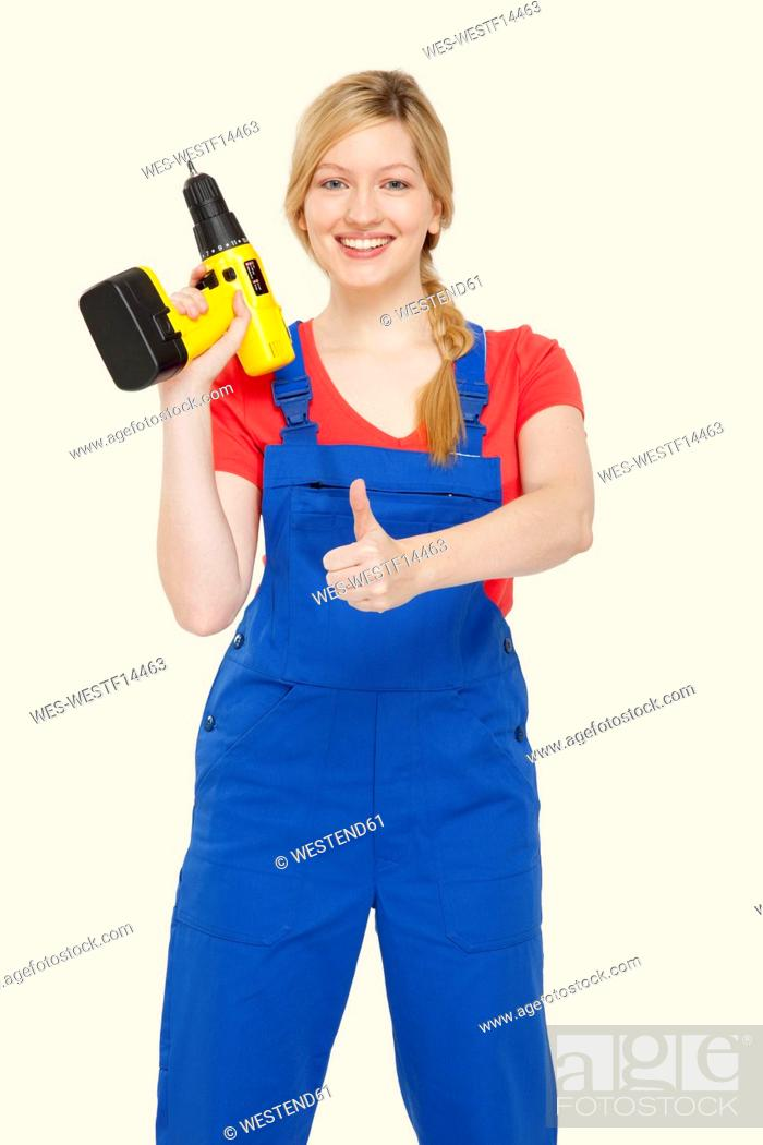 Stock Photo: Young woman holding power drill, showing thumbs up sign, portrait.