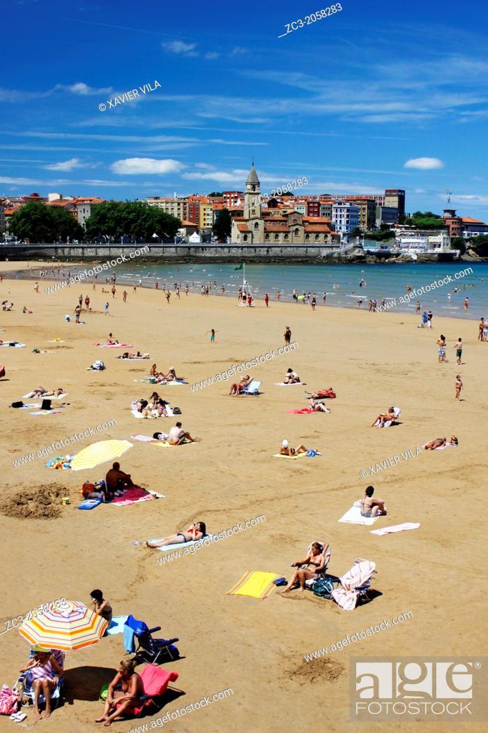 Photo de stock: Beach of San Lorenzo with umbrellas and San Pedro Church, city of Gijon, Asturias, Spain.